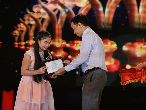 Thiện Nhân được ông Đỗ Danh Phương - Tổng biên tập Báo Người Lao Động trao tượng Mai Vàng và giấy chứng nhận.