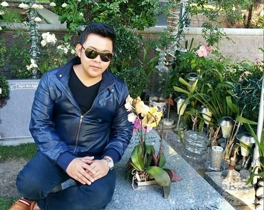 Ảnh Quang Lê ngồi trên mộ bị chỉ trích. Ảnh: Facebook NV
