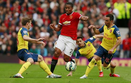 Valencia (25) đi bóng giữa hàng thủ Arsenal