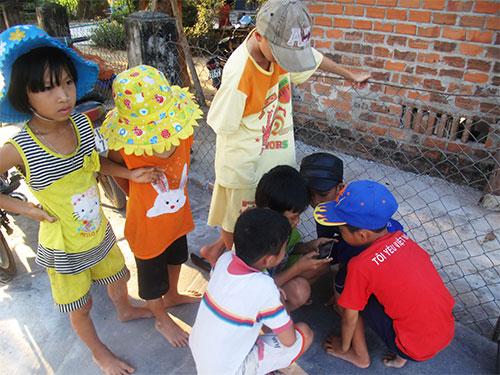 Thiếu bố mẹ, những nhóm trẻ mải mê với các trò chơi trên điện thoại ở thôn Tân Mỹ, xã Hòa Phú, huyện Tây Hòa, tỉnh Phú Yên Ảnh: HỒNG ÁNH