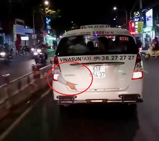 Cánh tay lòi khỏi đuôi taxi khiến nhiều người không khỏi rùng mình (ảnh cắt từ clip)