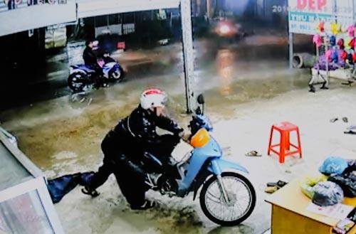 Hai đối tượng mặc áo mưa trộm xe máy của anh Hoàng Xuân Nam (ảnh trích xuất từ camera)