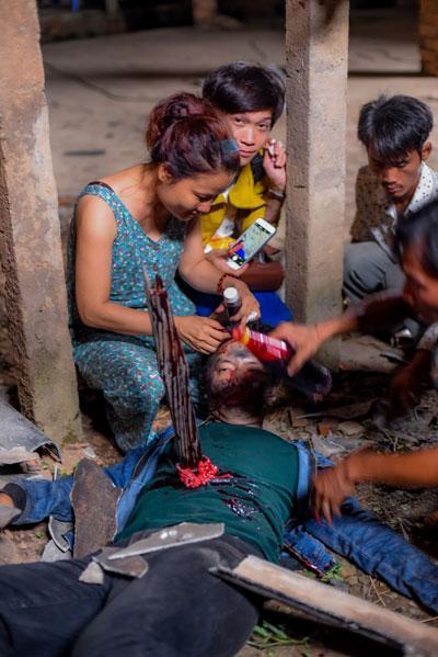 """Nhân viên Bích Liên hóa trang cho diễn viên Thái Hòa trong phim """"Người đàn bà ngủ trên mái nhà"""". (Ảnh do đoàn phim cung cấp)"""