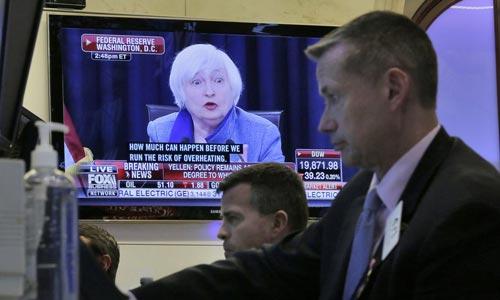Các nhà giao dịch làm việc tại TP New York - Mỹ trong khi Chủ tịch FED Janet Yellen thông báo quyết định tăng lãi suất cơ bản Ảnh: AP