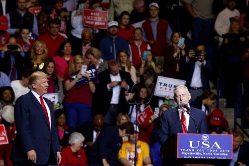 Tỉ phú Donald Trump lắng nghe tướng về hưu James Mattis phát biểu tại cuộc tuần hành ở TP Fayetteville hôm 6-12 Ảnh: REUTERS