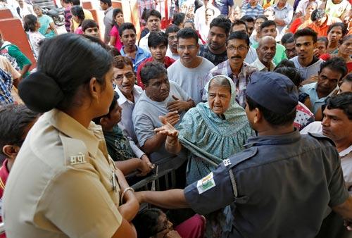 Người dân cãi vã với lực lượng an ninh sau khi bị ngăn vào một ngân hàng ở TP Mumbai hôm 12-11 Ảnh: REUTERS