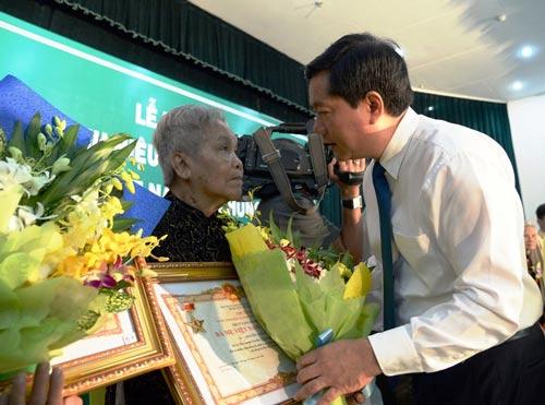 Bí thư Thành ủy TP HCM Đinh La Thăng trao bằng và tặng hoa cho một bà mẹ Việt Nam anh hùng