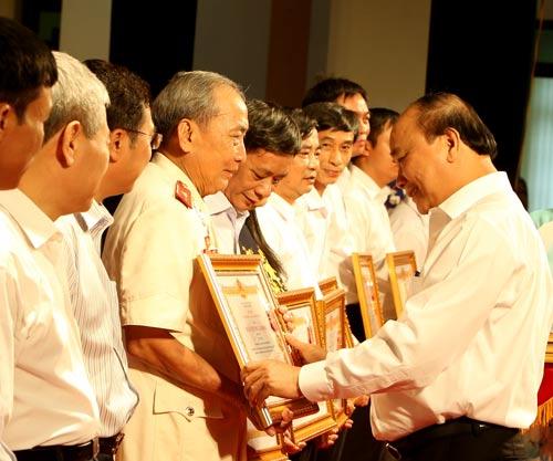 Thủ tướng Nguyễn Xuân Phúc trao tặng Huân chương Lao động hạng ba của Chủ tịch nước cho các cá nhân có thành tích xuất sắc trong công tác thực hiện dự án di dân, tái định cư thủy điện Sơn La - Ảnh: TTXVN