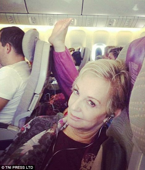 Người phụ nữ ngán ngẩm vì hành vi thiếu ý thức của hành khách bên cạnh. Ảnh: TNI Press LTD