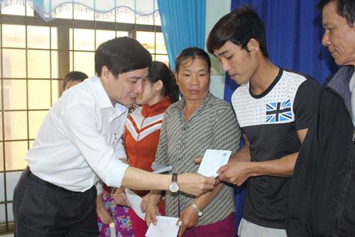 Ông Bùi Văn Cường, Chủ tịch Tổng LĐLĐ Việt Nam, trao tiền hỗ trợ người dân vùng lũ xã An Hiệp, huyện Tuy An, tỉnh Phú Yên Ảnh: HỒNG ÁNH