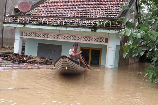 Tỉnh Phú yên chịu thiệt hại nặng nề do mưa lũ khi ít nhất đã có 7 người chết và 1 người mất tích - Trong ảnh: một người dân ở xã An Định, huyện Tuy An, tỉnh Phú Yên vội vã chạy lũ - Ảnh: HỒNG ÁNH