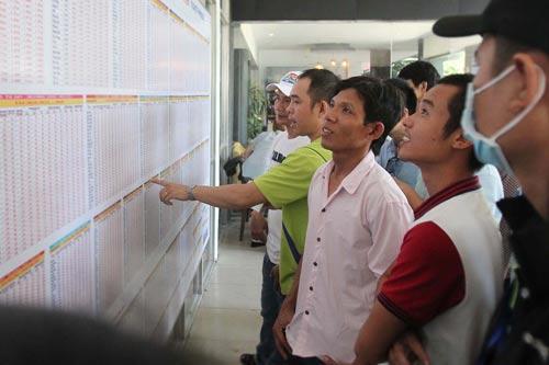 Nhiều hành khách xem bảng giá tàu Tết 2017 tại ga Sài Gòn Ảnh: HOÀNG TRIỀU