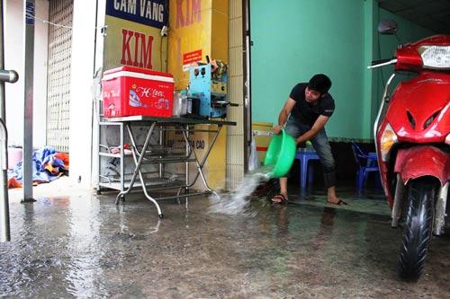 Mưa cộng triều cường đã đẩy nhiều nhà dân vào thế… tát nước chống ngập Ảnh: GIA MINH