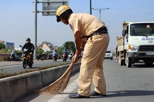 CSGT đang quét dọn đá dăm trên đường Phạm Văn Đồng