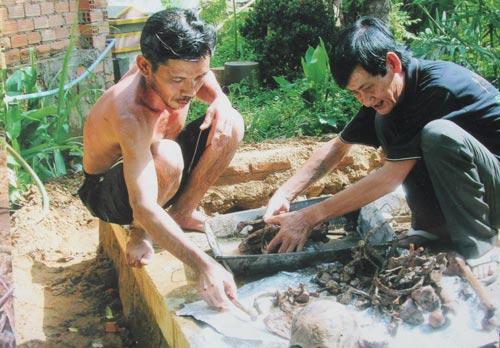 Ông Ba Oanh (phải) giúp hốt cốt cho những người có hoàn cảnh khó khăn. (Ảnh do gia đình cung cấp)