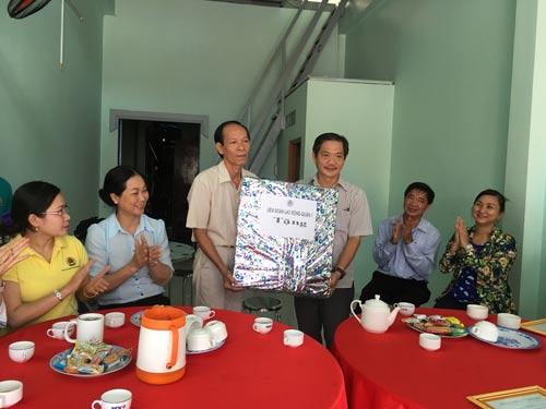 Ông Nguyễn Phi Hổ, Phó Ban Chính sách Pháp luật - LĐLĐ TP HCM (hàng đứng; bên phải), trao mái ấm Công đoàn cho đoàn viên khó khăn tại TP Cao Lãnh, tỉnh Đồng Tháp