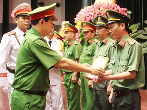 Đại tá Đinh Thanh Nhàn, Phó Giám đốc Công an TP HCM, trao giấy khen cho các tập thể, cá nhân có thành tích xuất sắc trong Phong trào Toàn dân bảo vệ an ninh Tổ quốc