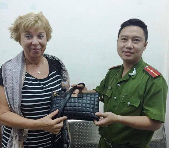 Công an trao trả lại tài sản cho bà Anna Milasevic khi bị 2 tên cướp giật túi xách trên đường Bùi Viện vào tháng 3-2016. - Ảnh: Sỹ Hưng