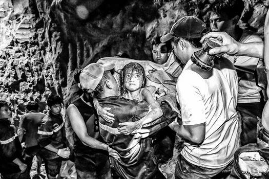 Trung tá Lê Minh Dũng không để phóng viên chụp hình chân dung mình. Đây là tấm ảnh lúc trung tá Dũng ẵm bé gái thoát khỏi giếng sâu hàng chục mét sau nhiều giờ đào bới để tiếp cận bé