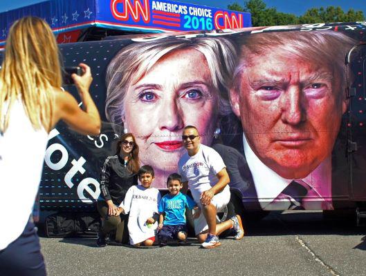 Một gia đình chụp hình trước chân dung hai ứng viên tổng thống Mỹ tại khuôn viên Trường ĐH Hofstra hôm 25-9 Ảnh: Newsday