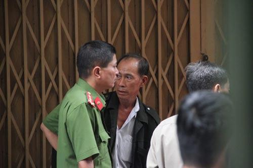 Ông Trung (áo khoác đen) như chết lặng khi biết các con và cháu ngoại đều đã thiệt mạng trong vụ cháy Ảnh: Gia Minh