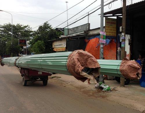Chiếc xe ba gác chở cuộn tôn dài hơn chục mét nghênh ngang lao trên đường Ảnh: GIA MINH