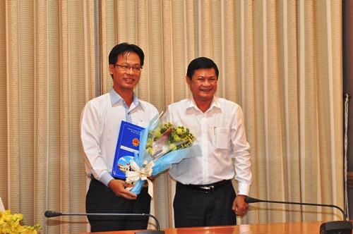 Phó Chủ tịch UBND TP HCM Huỳnh Cách Mạng (phải) trao quyết định cho đồng chí Đậu An Phúc. Ảnh: Bảo Ngọc