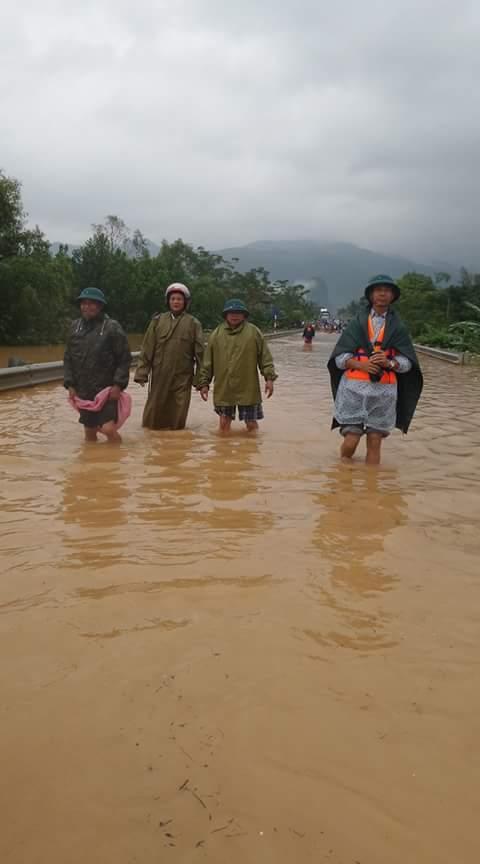 Cán bộ xã Đức Hóa lội nước giúp dân tránh lũ (ảnh Ngọc Hà)