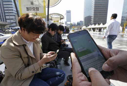 Người đàn ông Hàn Quốc (bên phải) đang sử dụng ứng dụng tin nhắn KakaoTalk Ảnh: AP