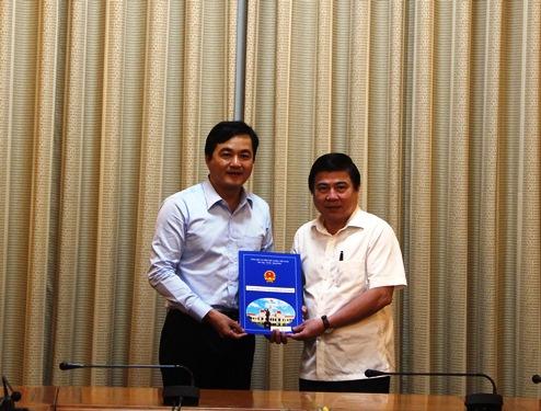 Chủ tịch UBND TP Nguyễn Thành Phong trao quyết định điều động và bổ nhiệm cho ông Bùi Tá Hoàng Vũ. Ảnh: Bảo Ngọc