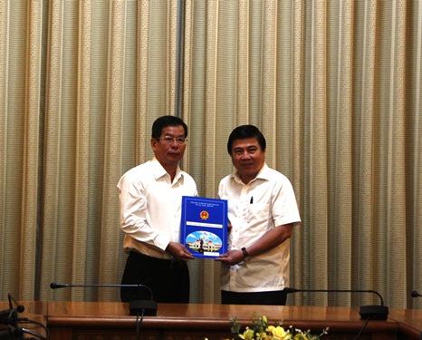 Chủ tịch UBND TP Nguyễn Thành Phong trao quyết định điều động và bổ nhiệm ông Nguyễn Hữu Việt. Ảnh: Bảo Nghi