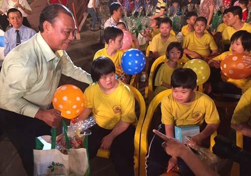 Ông Lê Tấn Hùng, Tổng Giám đốc Tổng Công ty Nông nghiệp Sài Gòn, trao tặng quà cho các em khuyết tật