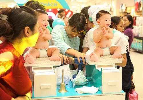 Một bà mẹ dùng quả tạ nặng 2 kg nhấn mạnh lên miếng khăn giấy trên tã Pampers baby-dry để kiểm chứng khả năng khóa ẩm của tã