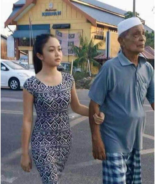"""Cặp đôi """"ông cháu"""" dắt tay nhau đi trên đường trước sự bàn tán không ngớt của những người xung quanh."""