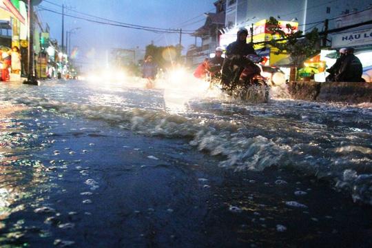 Nước dâng cao và chảy cuồn cuộn trên đường Huỳnh Tấn Phát