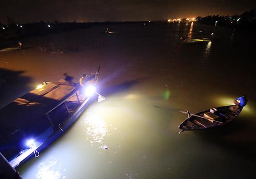 Người dân chèo thuyền ra giữa sông Đế Võng săn cá lệch. Ảnh: Nguyễn Đông.