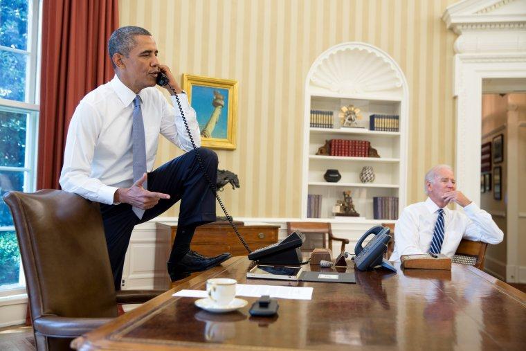 Ông Obama nói chuyện điện thoại với Chủ tịch Hạ viện (khi đó) John Boehner trong khi ông Biden ngồi nghe trong phòng Bầu dục. Ảnh chụp ngày 31-8-2013: NHÀ TRẮNG