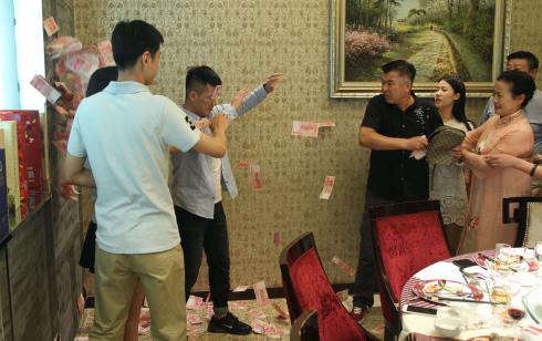 Bố vợ (áo đen) ném cả sấp tiền vào mặt cậu con rể tương lai (áo xanh, quần đen) vì cho rằng anh này không thật thà, đào mỏ.Ảnh: Weibo.