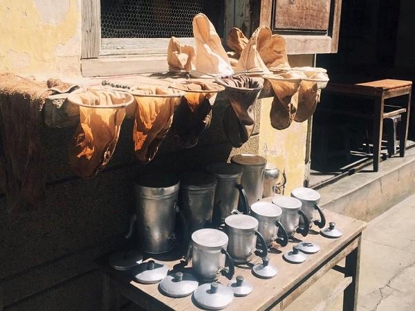 Ấm đun, vợt cà phê sưởi nắng ngay bên ngoài quán.