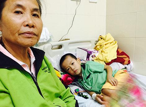 Bé Nguyễn Đình Dũng nằm đau đớn trên giường, bên cạnh là bà nội.