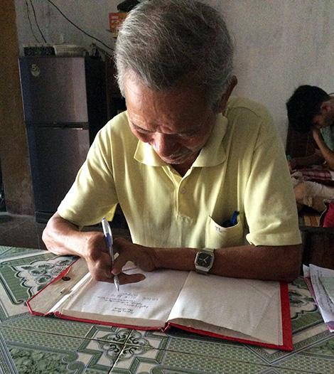 Ông Thiểu thể hiện khả năng viết chữ đẹp của mình.