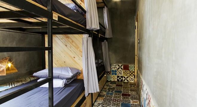 Phòng tập thể có giường tầng gọn gàng, màn che kín đáo. Phòng giường đôi 450.000 đồng một đêm, phòng tập thể 150.000 đồng một đêm. Hostel phục vụ 24 giờ, điều hòa đầy đủ, Wi-Fi phủ sóng. Ảnh: Agoda.