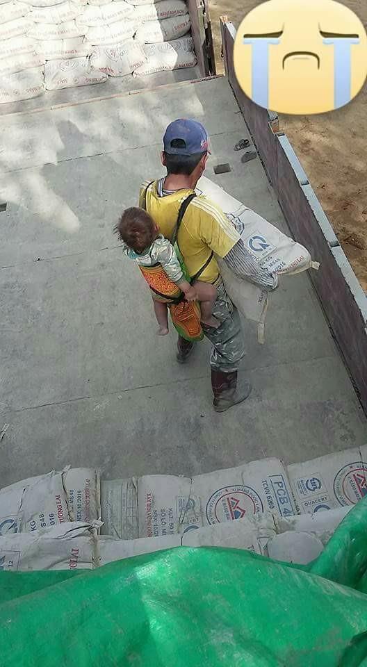 Hình ảnh người cha vừa địu con vừa vác xi măng tại công trường. Theo chia sẻ của người chụp, công trường này ở Lạng Sơn.
