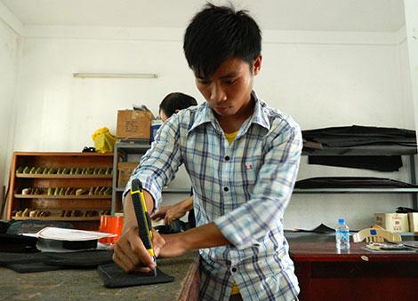 Anh Khieophone tập trung thực hành thao tác cắt đế giày.