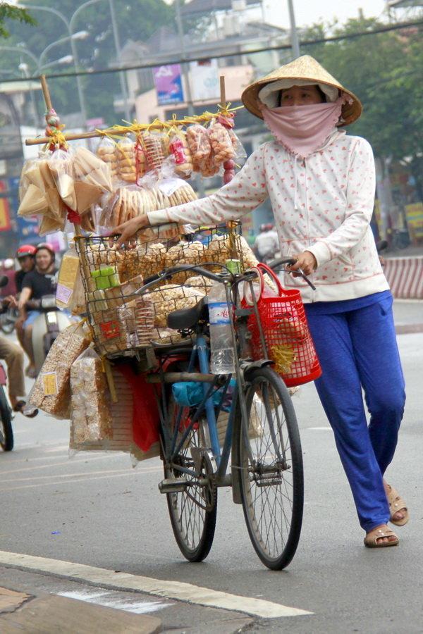 Chị bán bánh dạo với xe bán các loại bánh bình dân, trong đó có bánh chao - Ảnh: BẢO KHÔI