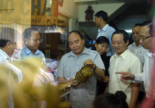 Thủ tướng mua chiếc giò lụa ở một cơ sở chế biến thực phẩm phường Tân Thành (Phường 7, Quận 11). Ảnh: VGP/Quang Hiếu