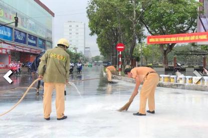 Lực lượng CSGT Công an TP Cần Thơ giúp chủ xe rửa sạch sơn trên mặt đường. Ảnh: Facebook