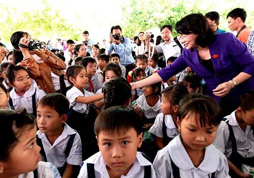 Bà Đặng Thị Ngọc Thịnh - Ủy viên BCH Trung ương Đảng, Phó Chủ tịch nước trao tặng sữa cho các em Trường tiểu học Hòa Bình A, xã Hòa Bình, Trà Ôn, Vĩnh Long