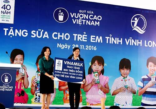 Bà Bùi Thị Hương Giám đốc điều hành Vinamilk (bên trái) trao tặng 800 triệu đồng cho trẻ em Vĩnh Long)
