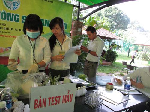 Lực lượng chức năng lấy mẫu xét nghiệm nhanh chất lượng rau quả tại chợ phiên